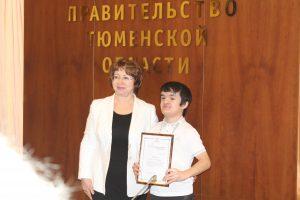 Заместитель губернатора Тюменской области Лариса Теплоухова награждает студента ТИУ Руслана Абдулина